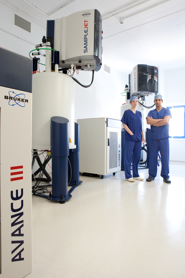 Photo of two surgeons standing next to two of the new 600 MHz NMR spectrometers