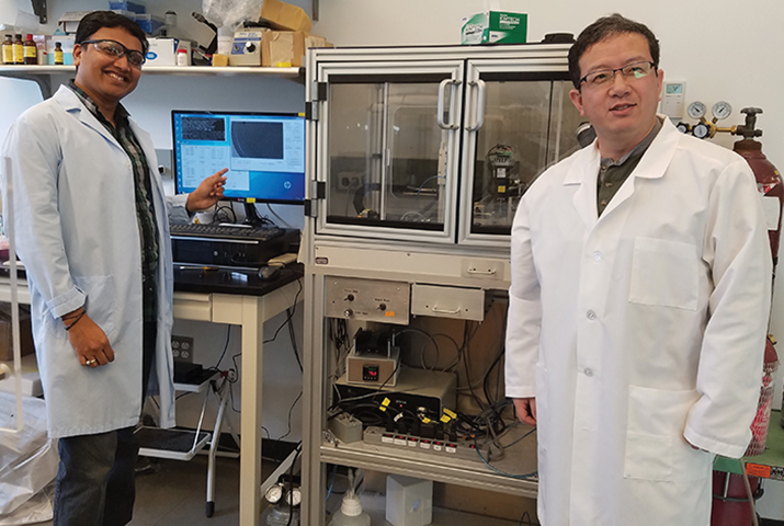 The Spotiton robot operated by Venkata Dandey (left) and Hui Wei (right) in the Carragher lab.